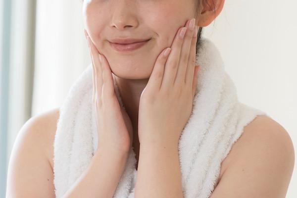 タオルを首にかけてお肌の調子を確かめている女性