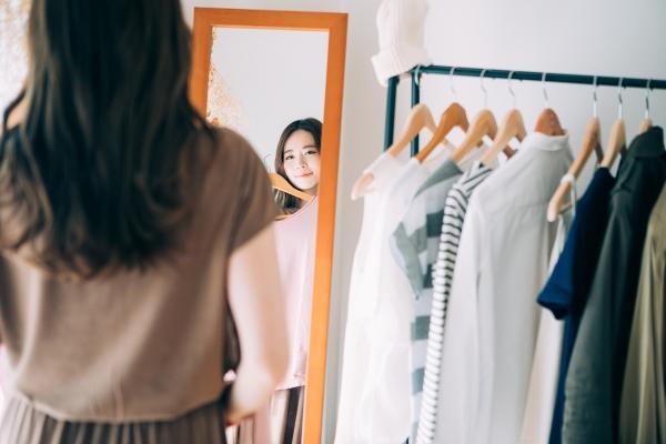 鏡の前で洋服を当ててみる女性